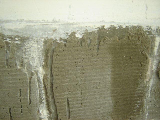 Тонкий слой плиточного клея на бетонной стене