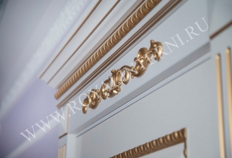 Золотой декор наличников и сандрика белой двери